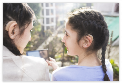 Two girls wearing hearing aids in conversation